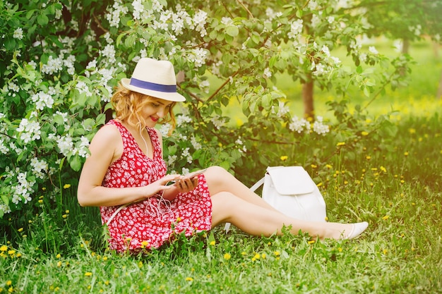 Молодая красивая девушка сидит в яблоневом саду, слушает музыку