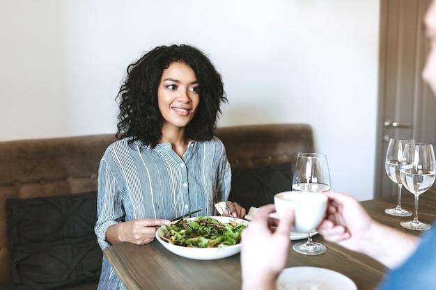 친구와 함께 레스토랑에 앉아서 샐러드를 먹는 젊은 아름 다운 소녀. 레스토랑에서 점심 시간에 샐러드를 먹는 꽤 아프리카 계 미국인 아가씨