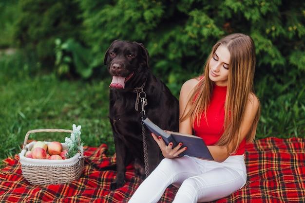 公園で彼女の黒犬のラブラドールと格子縞に座っている美しい少女。