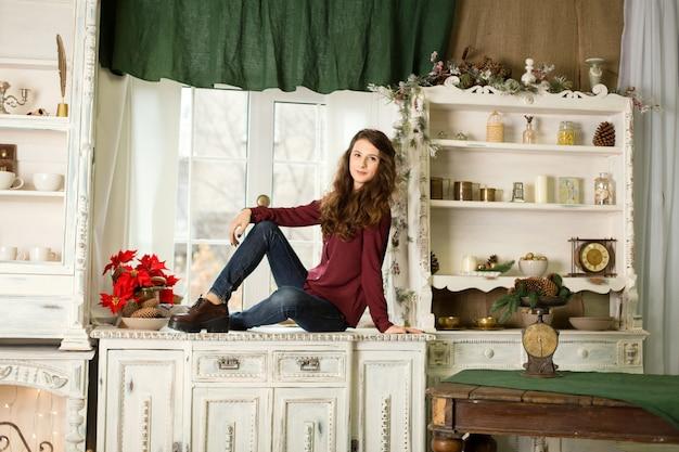 Молодая красивая девушка сидит на комоде у окна