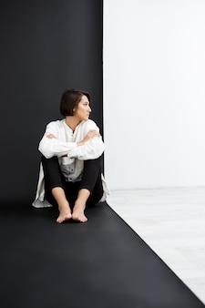 검은 색과 흰색 벽 위에 바닥에 앉아 젊은 아름 다운 소녀