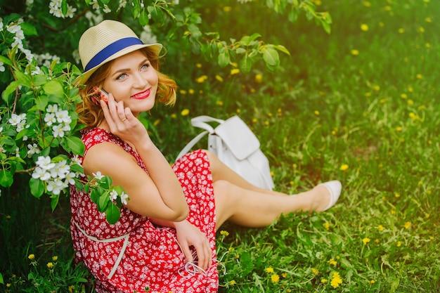 Молодая красивая девушка сидит на траве и разговаривает по телефону