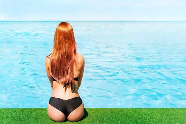 端に座って、明るい晴れた夏の日に海を背景に地平線を見ている若い美しい少女。ビーチで休んで日光浴をしている孤独な少女。テキスト用のスペース。