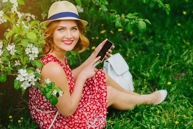 Молодая красивая девушка сидит на траве и показывает в телефоне