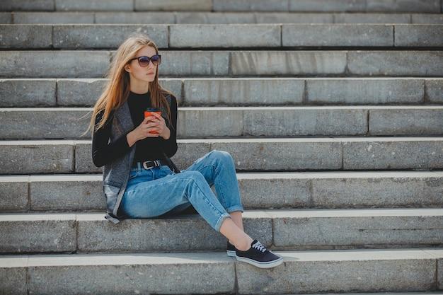 グラスにコーヒーを入れて階段に座っている若い美しい少女。