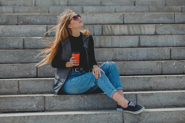 Молодая красивая девушка сидит на ступеньках с кофе в очках.