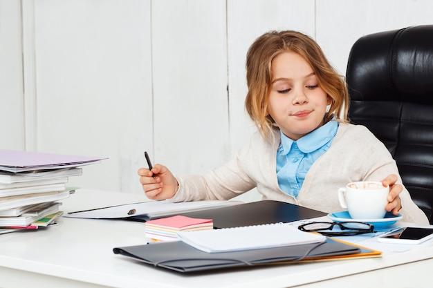 Giovane bella ragazza che si siede al posto di lavoro in ufficio.