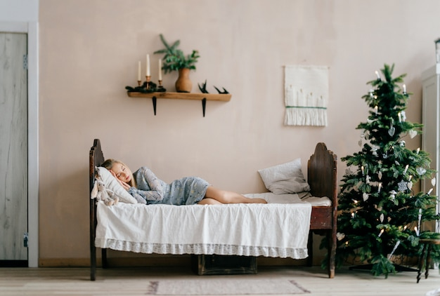 Young beautiful girl sleeping on bed with toy like child in room with christmas tree.