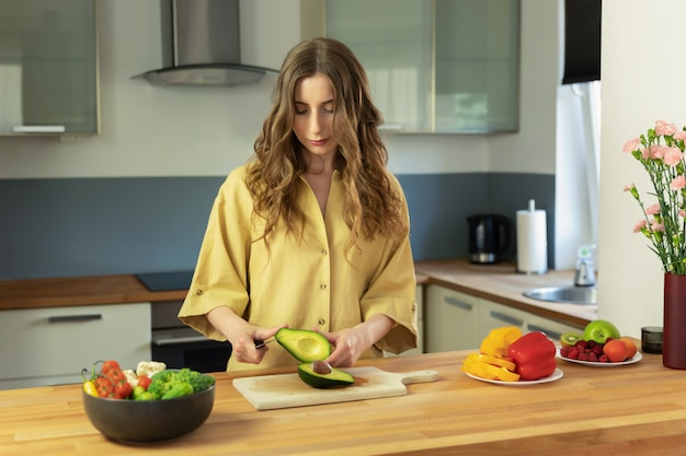 Young beautiful girl slices ripe avocado. a woman prepares a salad of fresh, healthy vegetables.