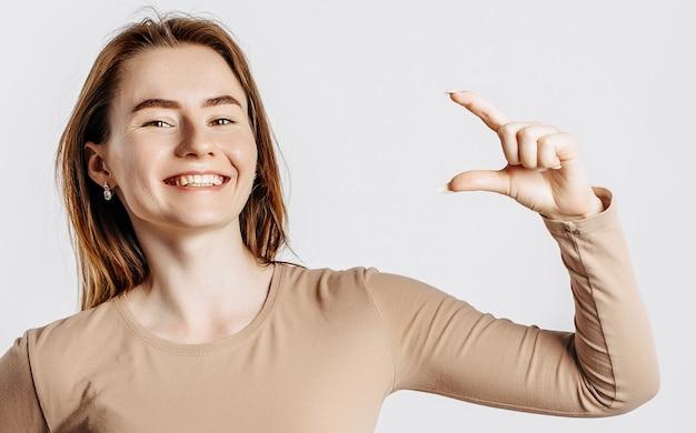 Молодая красивая девушка улыбается и показывает меру небольшого размера с жестом руки на белом изолированном фоне. женщина указывает на идею, место для рекламы. позитивная брюнетка в бежевом джемпере.