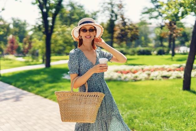 짚 핸드백과 커피를 일회용품에 들고 공원에서 행복한 산책을 하며 웃고 있는 젊은 아름다운 소녀...