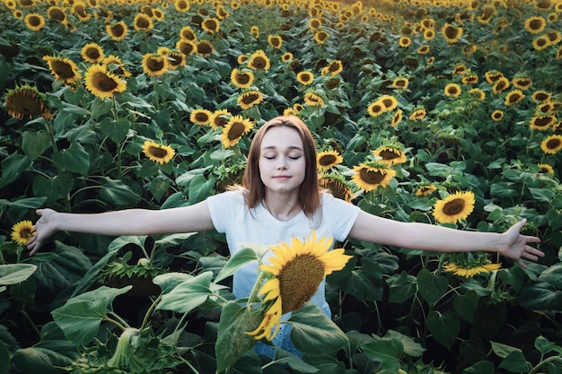 Young beautiful girl smiling and having fun in a sunflower field on a summer day with open arms.