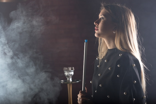 Young, beautiful girl smokes a hookah