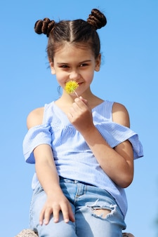 Молодая красивая девушка нюхает одуванчик на фоне голубого неба. фото высокого качества