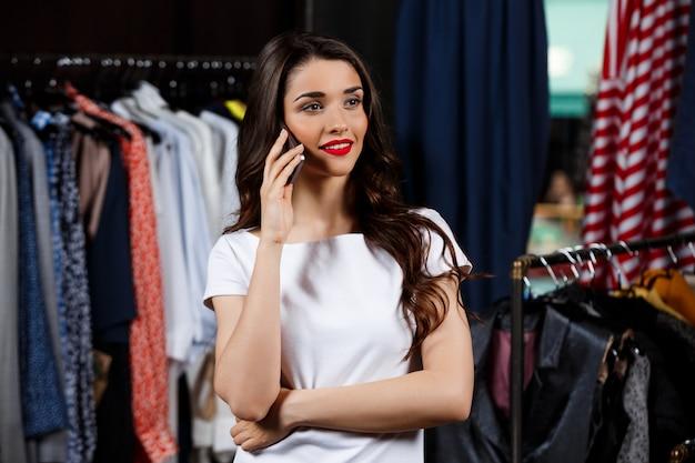 Giovane bella ragazza che parla sul telefono nel centro commerciale.