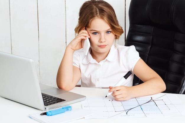Telefono parlante della giovane bella ragazza al posto di lavoro in ufficio.