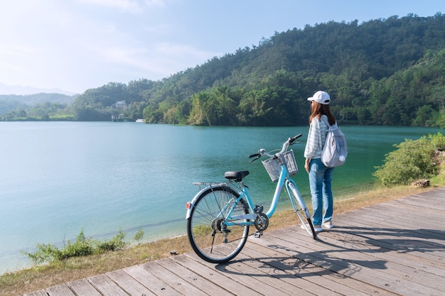 Young beautiful girl stand near a bicycle to looking at the view on bike trail at the lake in the morning