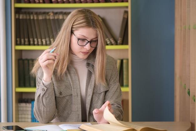 若い美しい女の子の学生は、図書館で本を扱っています。図書館での試験の準備