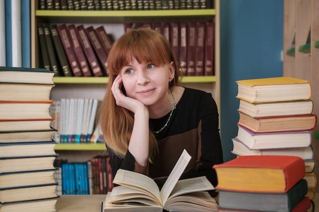 美しい少女の学生は、図書館で本を扱っています。
