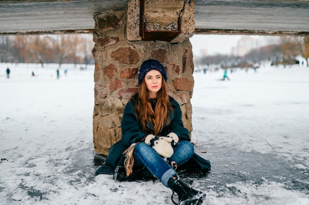 Young beautiful girl in stylish clothes with long hair sitting under bridge on ice on frozen lake in cold winter day in city park.