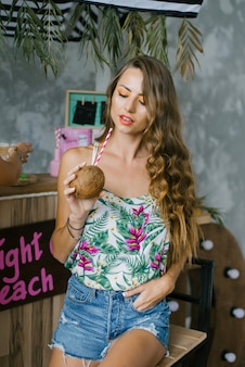 Young beautiful girl in summer beach clothes with bright makeup holding fresh coconut juice.