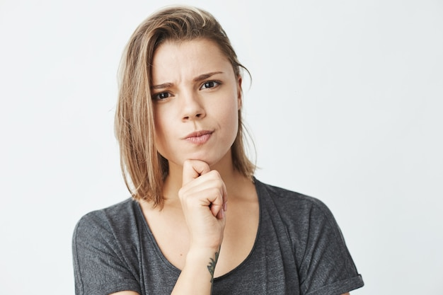 Young beautiful girl thinking with hand on chin frowning .
