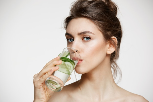 Young beautiful girl in towel looking at camera drinking water with cucumber slices over white background. healthy nutrition. beauty and skincare.