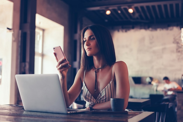 Young beautiful girl uses a laptop in cafe, surfing in internet