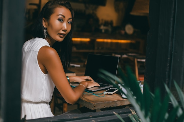Young beautiful girl uses a laptop in cafe, surfing the internet