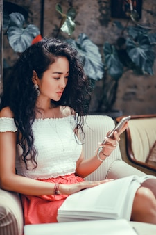 Young beautiful girl uses a smartphone on the street, surfing the internet
