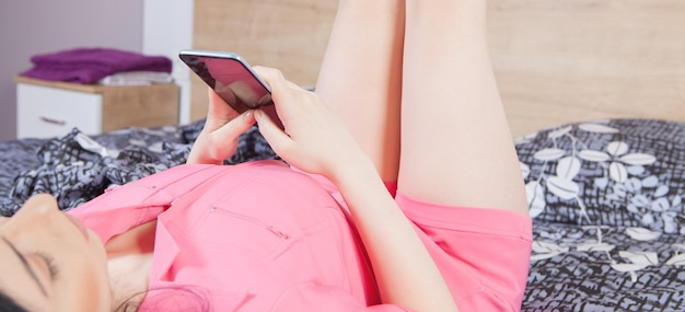 Young beautiful girl uses with the phone