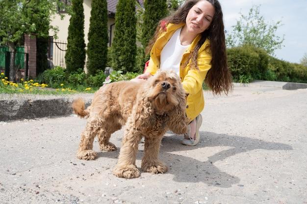 Молодая красивая девушка гуляет с собакой в солнечный день.