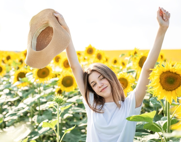 若い美しい少女は、咲くひまわりのあるフィールドで夏に歩きます