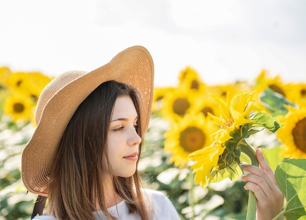 Young beautiful girl walks in the summer in a field with blooming sunflowers Premium Photo