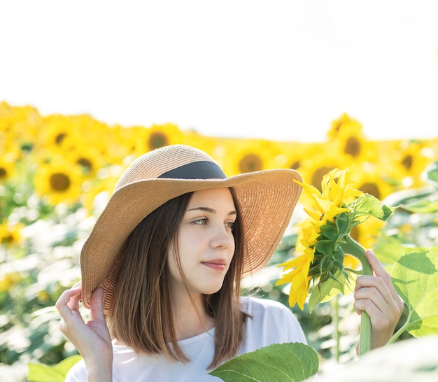 Young beautiful girl walks in the summer in a field with blooming sunflowers