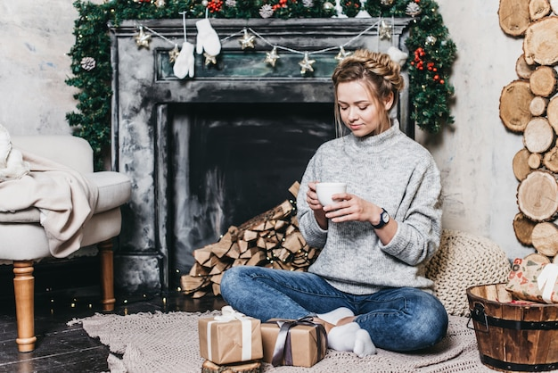 Young beautiful girl in a warm sweater near the fireplace. christmas and new year concept