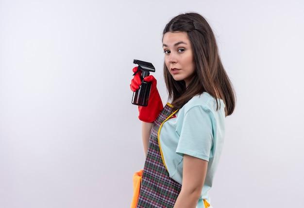 エプロンとゴム手袋を着用してクリーニングスプレーを保持し、白い背景の上のカメラを見て真面目な顔で横に立っている若い美しい少女