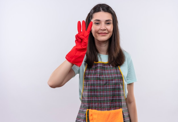 앞치마와 고무 장갑을 착용하고 손가락 3 번 미소로 가리키는 젊은 아름다운 소녀