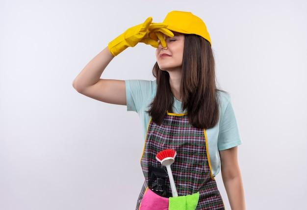 エプロン、キャップ、ゴム手袋を着用して悪臭に苦しんでいる指で鼻を閉じる若い美しい少女