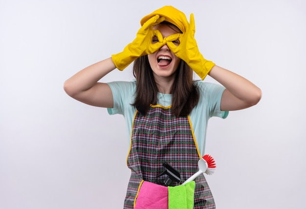 エプロン、キャップ、ゴム手袋を身に着けている若い美しい少女は、舌を突き出ている指を通して見ている指で双眼鏡のようなokの兆候をしています