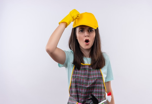 Молодая красивая девушка в фартуке, кепке и резиновых перчатках поднимает кулак и кричит с сердитым лицом