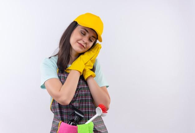 Giovane bella ragazza che indossa grembiule, berretto e guanti di gomma che tengono i palmi insieme appoggiando la testa sui palmi vuole dormire