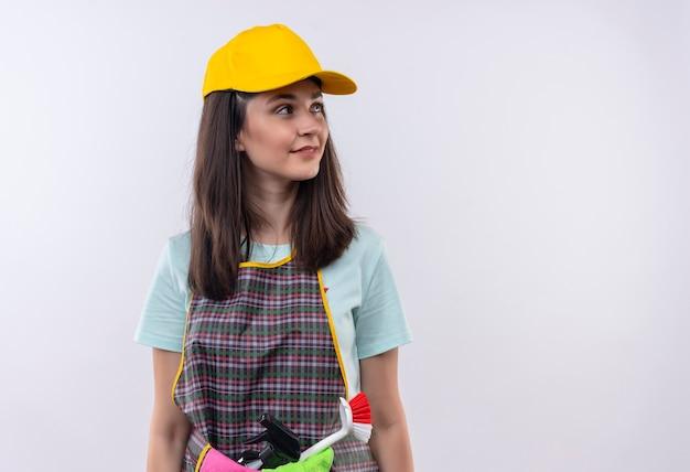Grembiule da portare della giovane bella ragazza, berretto e guanti di gomma che osserva da parte con un sorriso sicuro