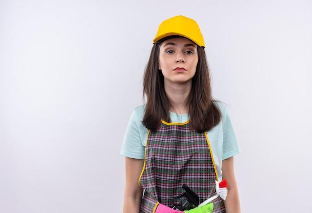 Giovane bella ragazza che indossa grembiule, berretto e guanti di gomma che guarda l'obbiettivo con seria espressione fiduciosa sul viso