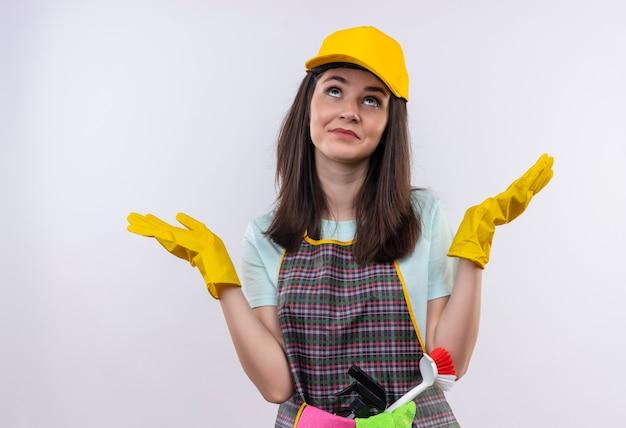 Giovane bella ragazza che indossa grembiule, berretto e guanti di gomma, alzando lo sguardo confuso diffondendo le braccia ai lati