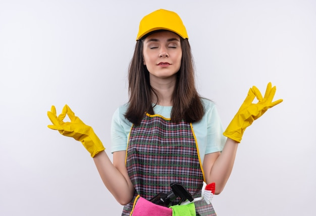 Young beautiful girl wearing apron, cap and rubber gloves relaxing with closed eyes making meditation gesture with fingers