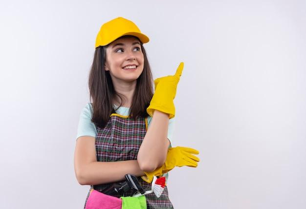 Giovane bella ragazza che indossa grembiule, berretto e guanti di gomma sorridendo allegramente rivolto verso l'alto con il dito indice
