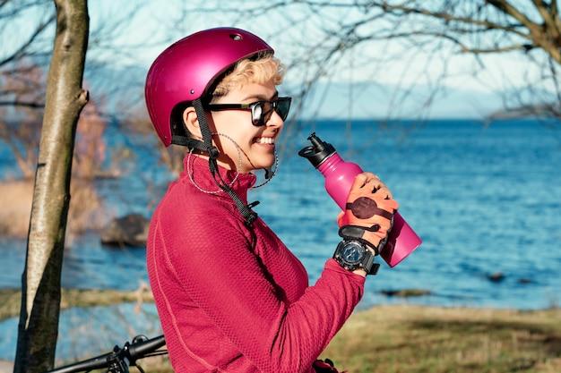 湖の近くで幸せな笑顔の水のボトルを飲む自転車のヘルメットを身に着けている若い美しい少女