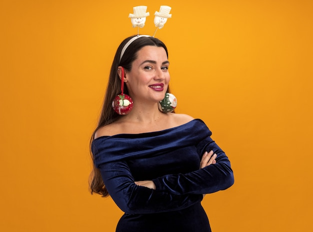 Young beautiful girl wearing blue dress and christmas hair hoop holding christmas balls on ears - isolated on orange wall