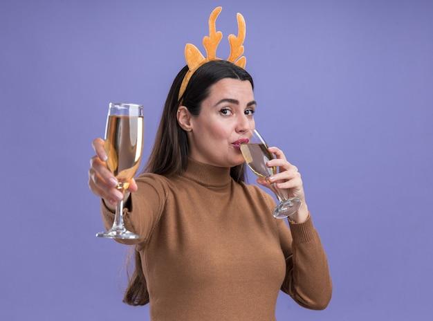 青い背景で隔離のカメラでシャンパングラスを差し出してクリスマスヘアフープと茶色のセーターを着ている若い美しい少女